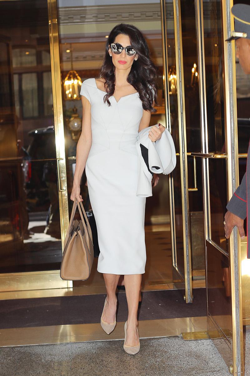 Η ΑΜάλ Κλούνεϊ με λευκό φόρεμα βγαίνει από ξενοδοχείο στη Νέα Υόρκη