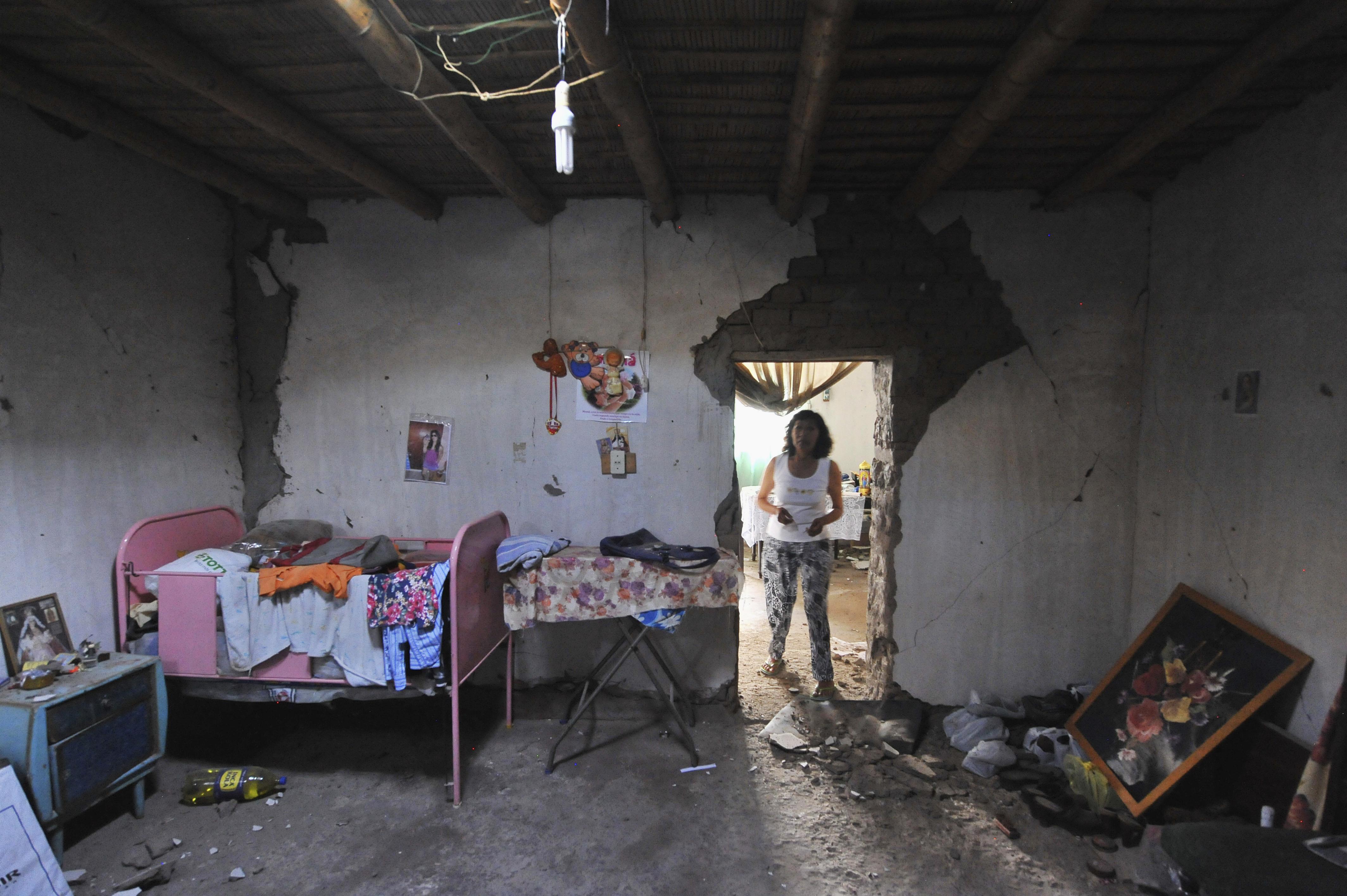 Μια γυναίκα παρατηρεί το κατεστραμμένο σπίτι της