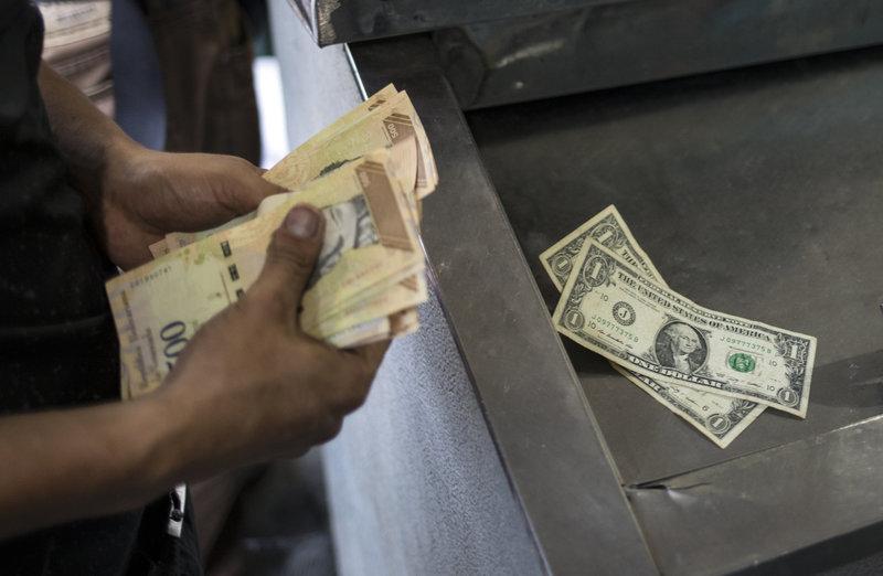 Άνδρας μετρά χαρτονομίσματα σε ATM στη Βενεζουέλα.
