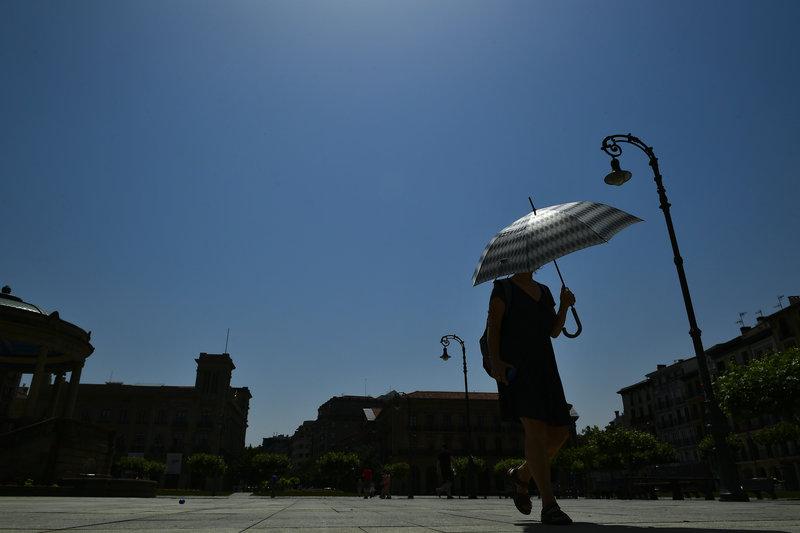 Ομπρέλα για να προστατευτεί απ' τον ήλιο επιστράτευσε αυτή η Ισπανίδα στην Παμπλόνα.