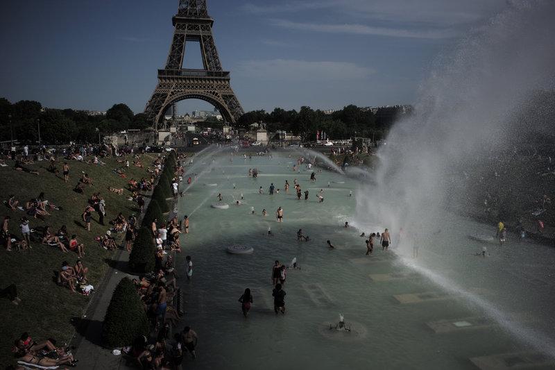 Κόσμος δροσίζεται στο συντριβάνι του Τροκαντερό στο Παρίσι.