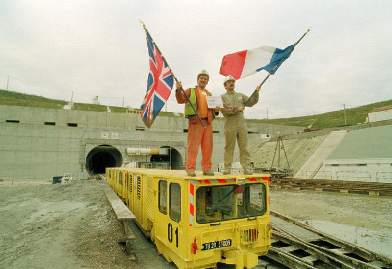 Γάλλος και Βρετανός εργάτης με σημαίες των χωρών τους στα χέρια την 1η Δεκεμβρίου 1990 όταν ενώθηκαν τα δύο τούνελ που διανοίγονταν παράλληλα σε ένα.
