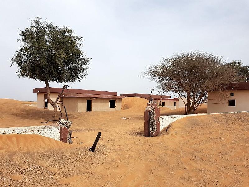 Εγκαταλειμμένα σπίτια, μισοβυθισμένα στην άμμο, στο χωριό φάντασμα Αλ Μαντάμ στα Ηνωμένα Αραβικά Εμιράτα.