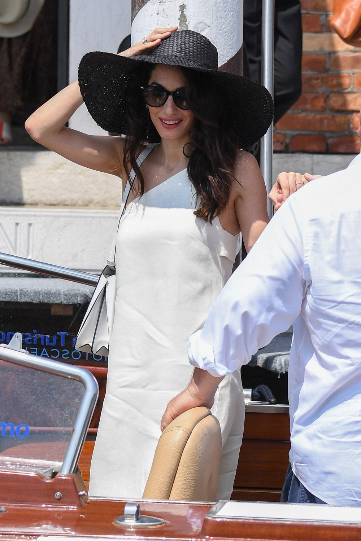 Η Αμάλ Κλουνεϊ με λευκό φόρεμα και πελώριο μαύρο καπέλο
