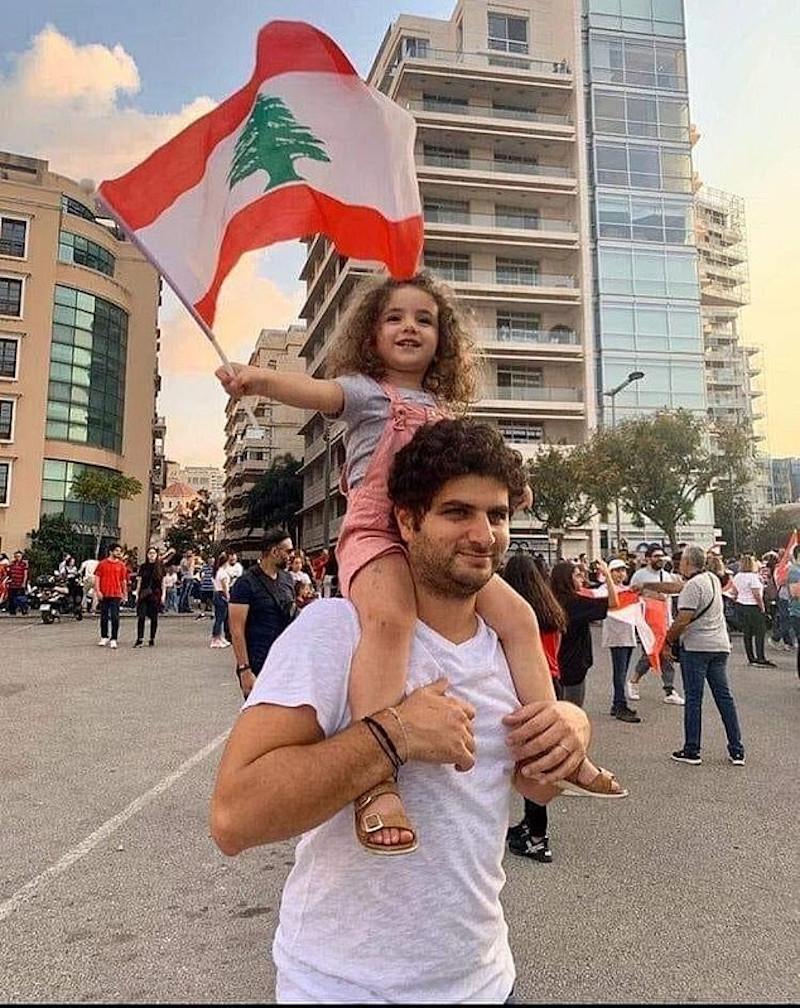 Η μικρή Αλεξάνδρα ανεμίζει τη σημαία του Λιβάνου ανεβασμένη στους ώμους του πατέρα της σε παλαιότερες ευτυχισμένες στιγμές