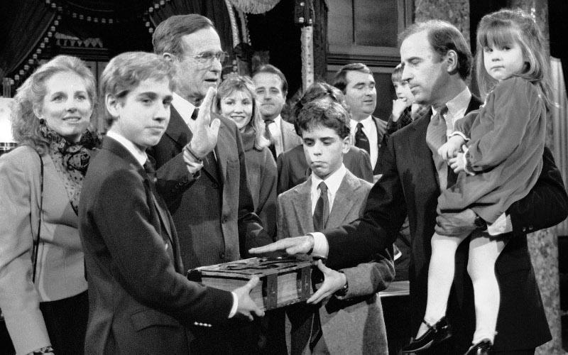 Ο Τζο Μπάιντεν στη διάρκεια τελετής στο Καπιτώλιο τον Ιανουάριο του 1985 με τον τότε αντιπρόεδρο των ΗΠΑ Τζορτζ Μπους. ΟΙ δυο γιοι του, Μπο και Χάντερ, κρατούν το Ευαγγέλιο για την πρόβα της ορκωμοσίας του ως γερουσιαστή.