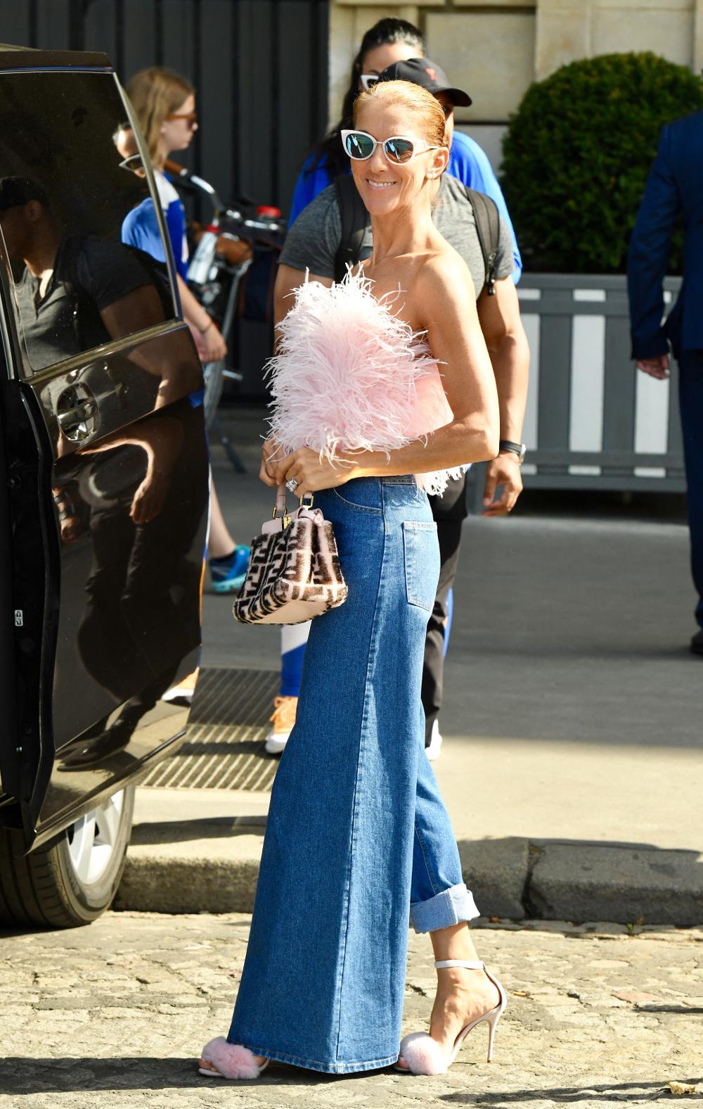 Με fluffy ροζ πέδιλα και φαρδύ τζιν παντελόνι με το ένα μπατζάκι ανασηκωμένο