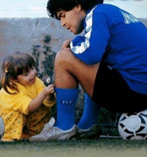 Ο Ντιέγκο Μαραντόνα με την στολή του και η κόρη του Τζιαννίνα με κίτρινο φόρεμα του δίνει ένα λουλούδι