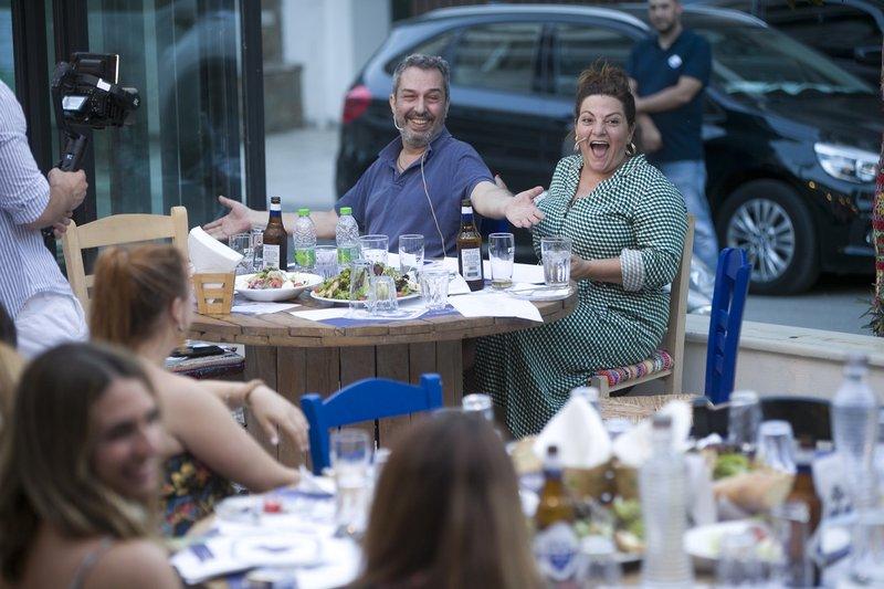 Η Βίκυ Σταυροπούλου και ο Χρήστος Χατζηπαναγιώτης χαμογελαστοί κάθονται σε τραπέζι