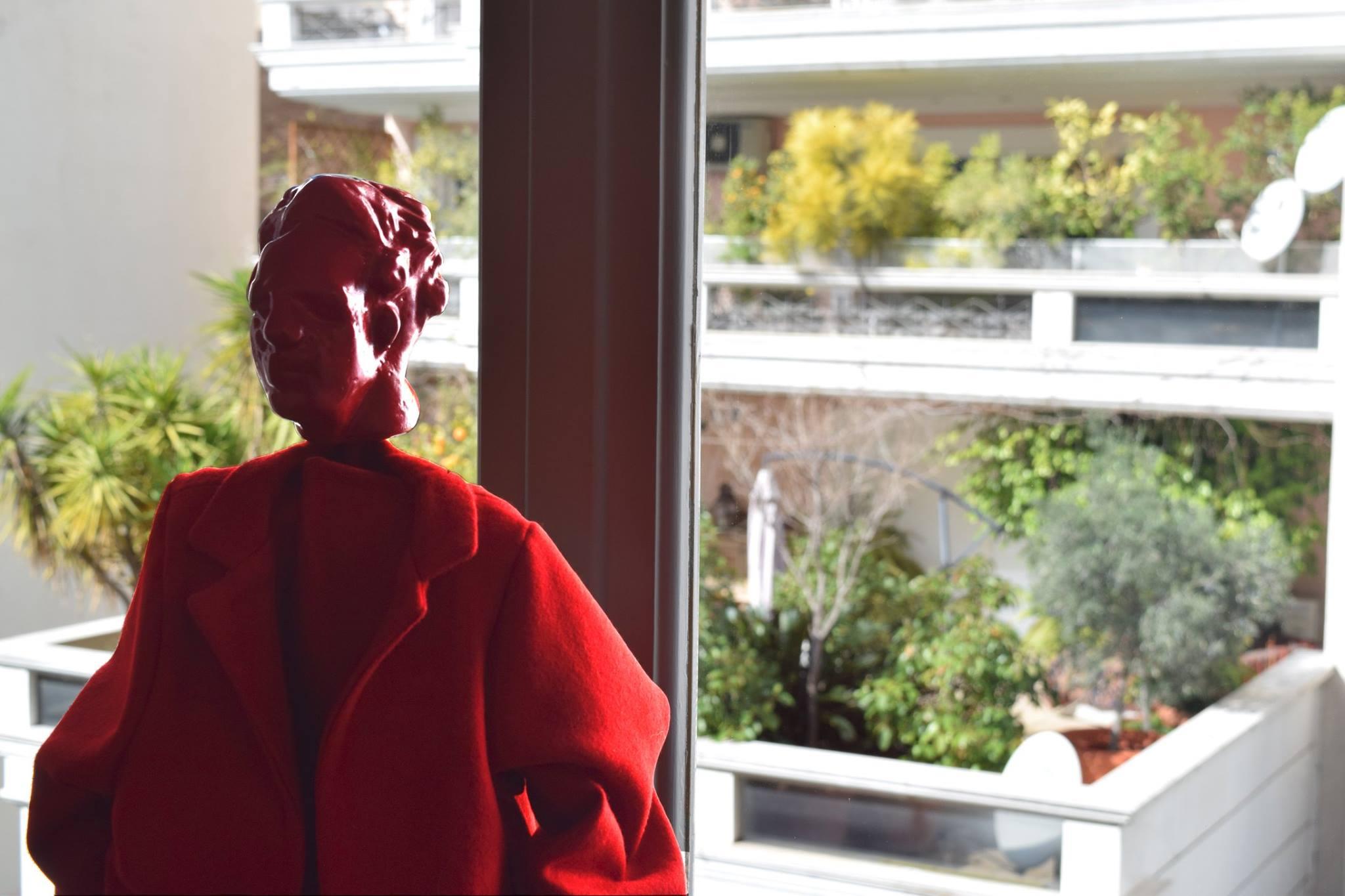 Κόκκινο γλυπτό στο παράθυρο