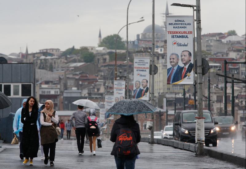 Κάτοικοι της Κωνσταντινούπολης περνούν μπροστά από αφίσες του υποψηφίου του Ερντογάν, Μπιναλί Γιλντιρίμ.
