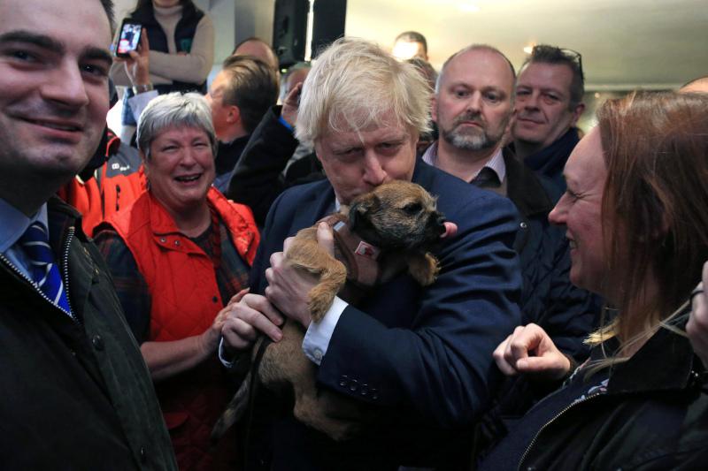 Ο Μπόρις Τζόνσον, αγκαλιά με τον σκύλο του Dilyn, δέχεται τα συγχαρητήρια για την μεγάλη νίκη των Τόρηδων στις εκλογές στη Βρετανία.