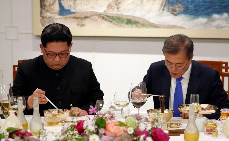 Ο Κιμ κι ο Νοτιοκορεάτης πρόεδρος Μουν Τζάε Ιν απολαμβάνουν βορεικορεατικό πιάτο με κρύα νουντλς από φαγόπυρο στη συνάντησή τους στα σύνορα των δύο χωρών τον Απρίλιο του 2018.