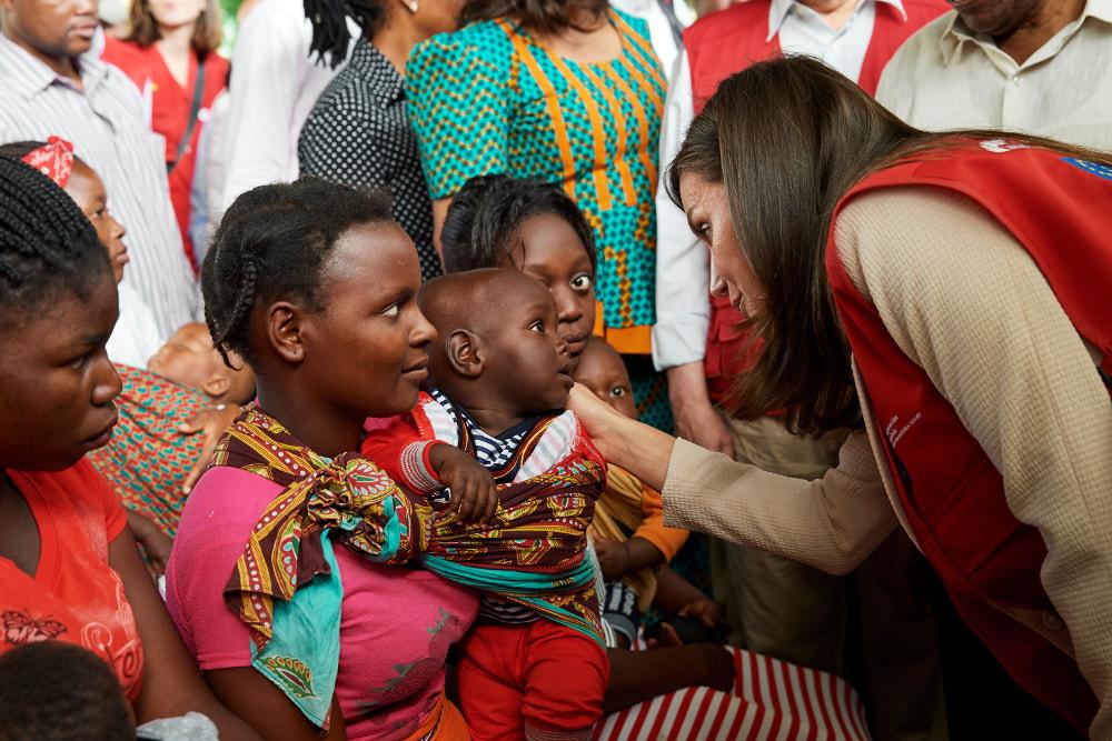 Η βασίλισσα Λετίθια φορώντας ένα μπεζ κουστούμι συνομιλεί με παιδιά στην Μοζαμβίκη