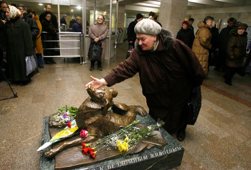 Γυναίκα χαϊδεύει άγαλμα σκύλο