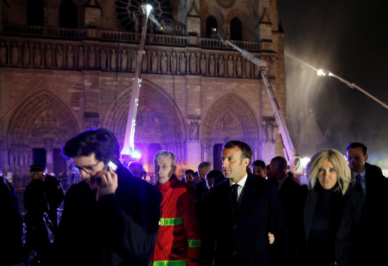 Ο  Γάλλος πρόεδρος Εμανουέλ Μακρόν και η Πρώτη Κυρία της χώρας, Μπριζίτ στον περίβολο της Παναγίας των Παρισίων.