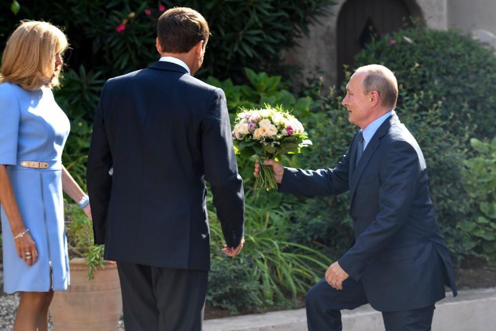 Ο Βλαντιμίρ Πούτιν προσφέρει μια ανθοδέσμη στην Πρώτη Κυρία της Γαλλίας