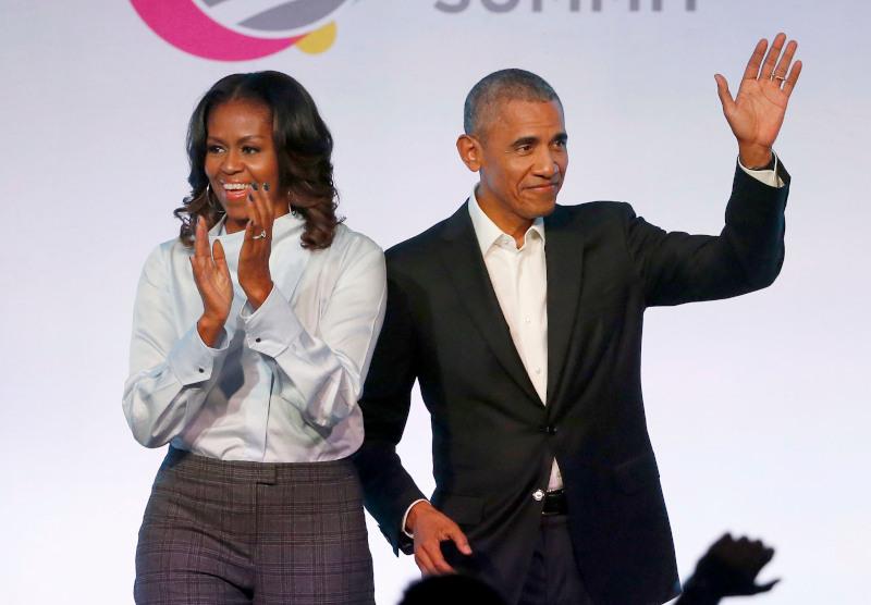 Η Μισέλ κι ο Μπαράκ Ομπάμα χαιρετούν το ακροατήριο σε εκδήλωση.