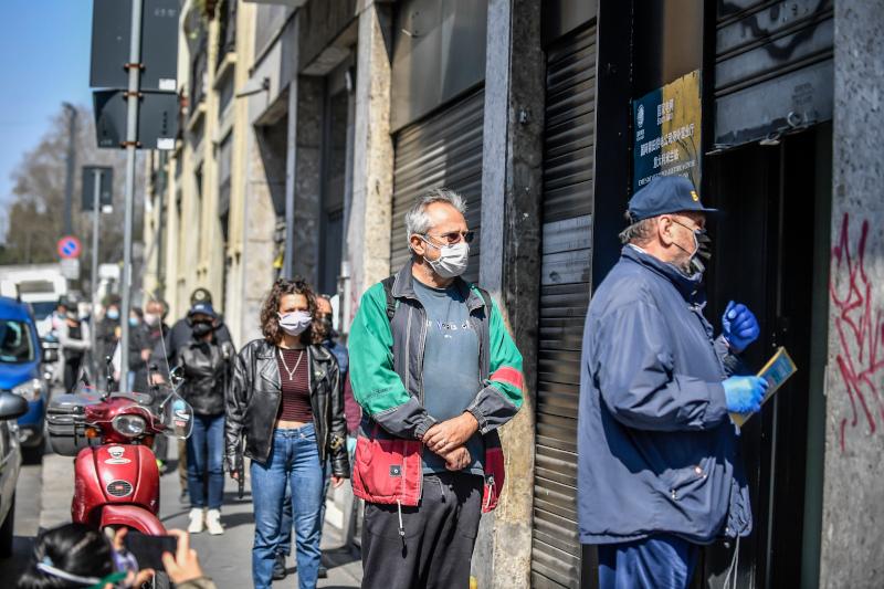 Ιταλοί περιμένουν στην ουρά σε τοποθεσία του Μιλανου για να παραλάβουν μάσκες, που έστειλε η Κίνα στο πλαίσιο ανθρωπιστικής βοήθειας.