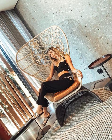 Η Μάιλι Σάιρους καθισμένη σε ψάθινη καρέκλα
