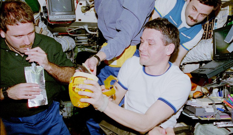 O Aμερικανός αστροναύτης Τζεφ Γκράνσφελντ πίνει μια γουλιά από ειδική συσκευασία, υπό το βλέμμα των Ρώσων συναδέλφων του Βαλέρι Κορσούν και Αλεξάντερ Καλέρι στο διαστημικό σταθμό Mir το 1997