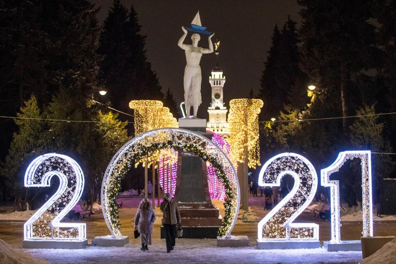 Μοσχοβίτες περνούν από φωταγωγημένη πύλη που αναγγέλλει την άφιξη του νέου έτους