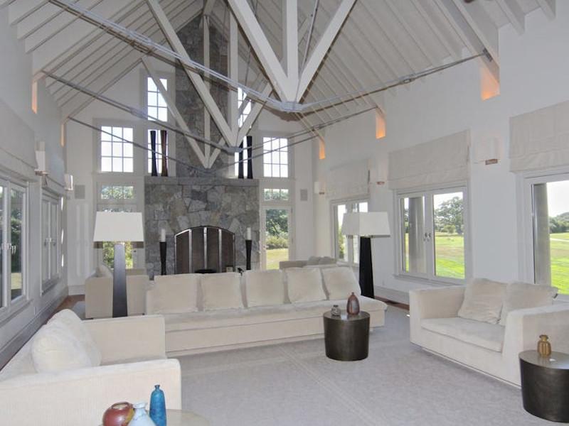 Το καθιστικό με την εντυπωσιακή ξύλινη οροφή, το πέτρινο τζάκι και το φως να τρυπώνει από παντού .