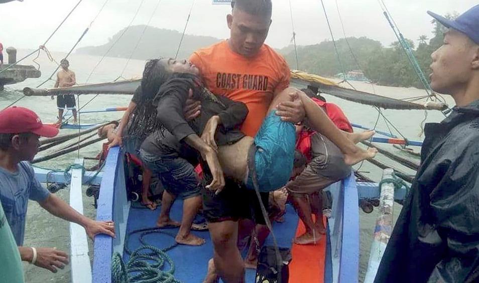 Μέλος της ακτοφυλακής των Φιλιππίνων μετφέρει στα χέρια έναν από τους επιζώντες του ναυαγίου.