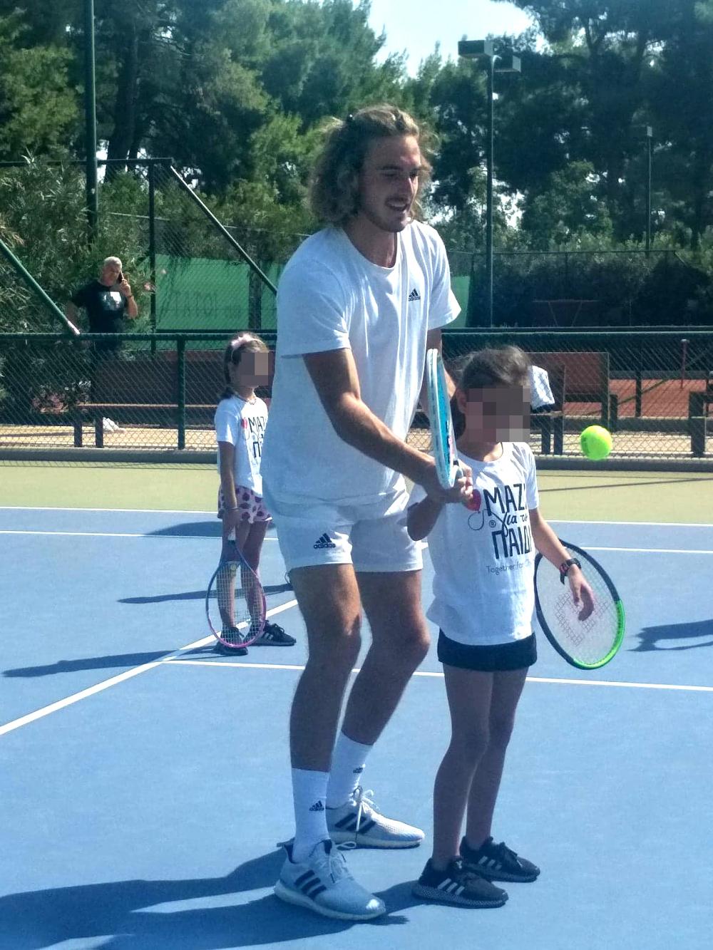 Ο Στέφανος Τσιτσιπάς δείχνει σε ένα κοριτσάκι πώς να κρατά την ρακέτα του τένις