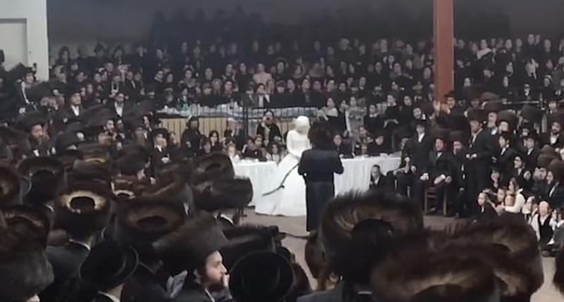 Ούτε ένας από το πλήθος των συνωστισμένων προσκεκλημένων δεν φορούσε μάσκα στη γαμήλια τελετή στη χασιδιτική συναγωγή στο Μπρούκλιν της Νέας Υόρκης