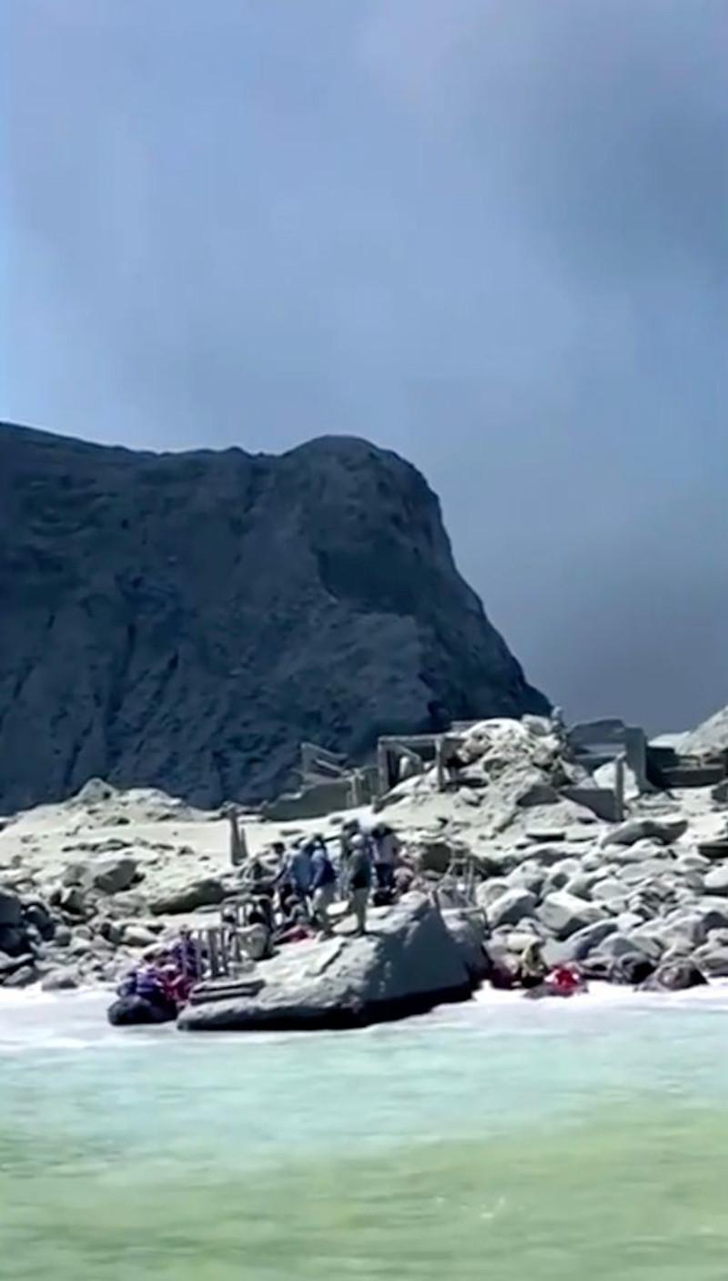Επιζώντες της έκρηξης του ηφαιστείου στο Λευκό Νησί της Νέας Ζηλανδίας, περιμένουν στην ακτή να τους απομακρύνουν.