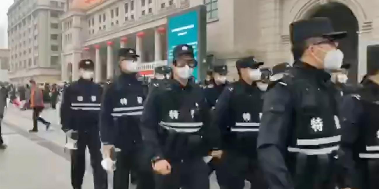 Αστυνομικοί με μάσκες περιπολούν σε δρόμο του Βουχάν.