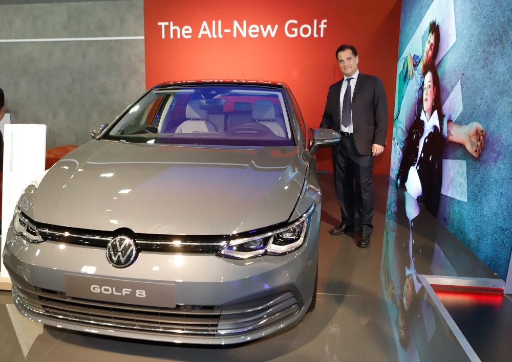 Ο Άδωνις Γεωργιάδης πλάι  στο ολοκαίνουριο, όπως λέει και το μπάνερ πίσω από το όχημα, Golf της VW