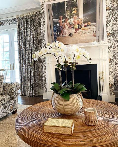 Το σαλόνι με το μαρμάρινο τζάκι και τις φλοράλ καφέ κουρτίνες