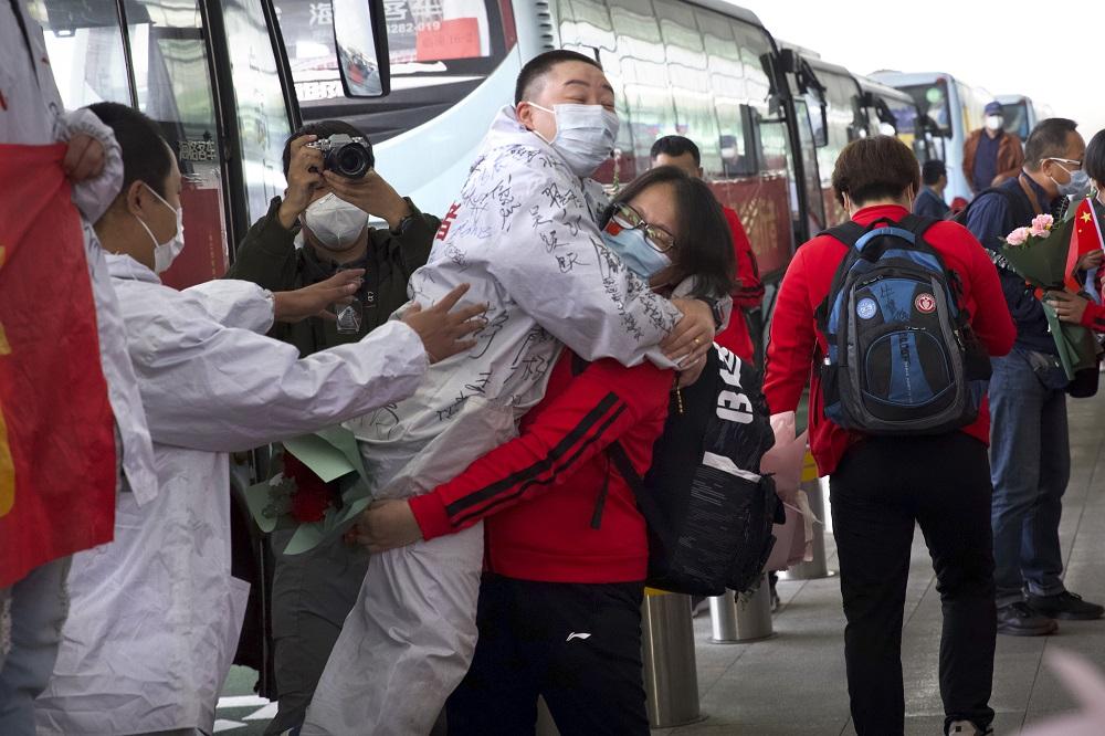 Γυναίκα αγκαλιάζει γιατρό με μάσκα στην Ουχάν