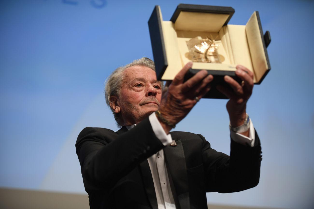 O Αλέν Ντελόν κρατά στα χέρια του το τιμητικό βραβείο για την καριέρα του, όπως το παρέλαβε στις Κάννες