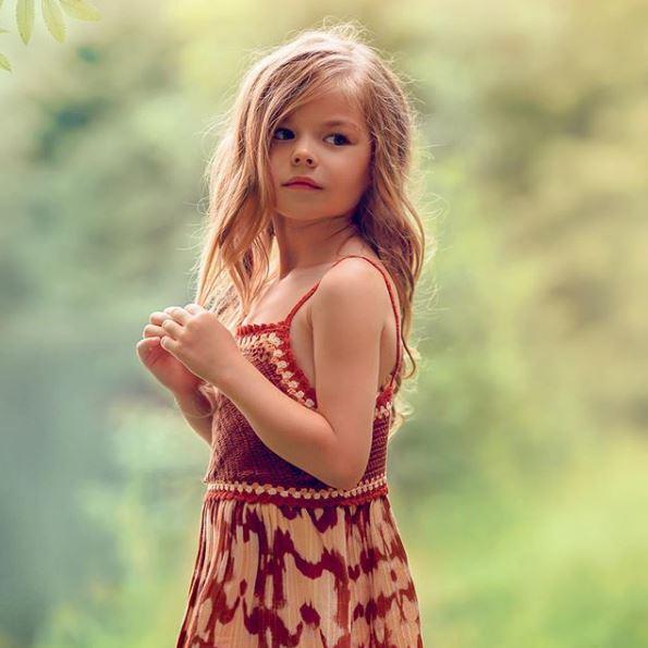 μικρό ξανθό κορίτσι με πλεκτό φόρεμα