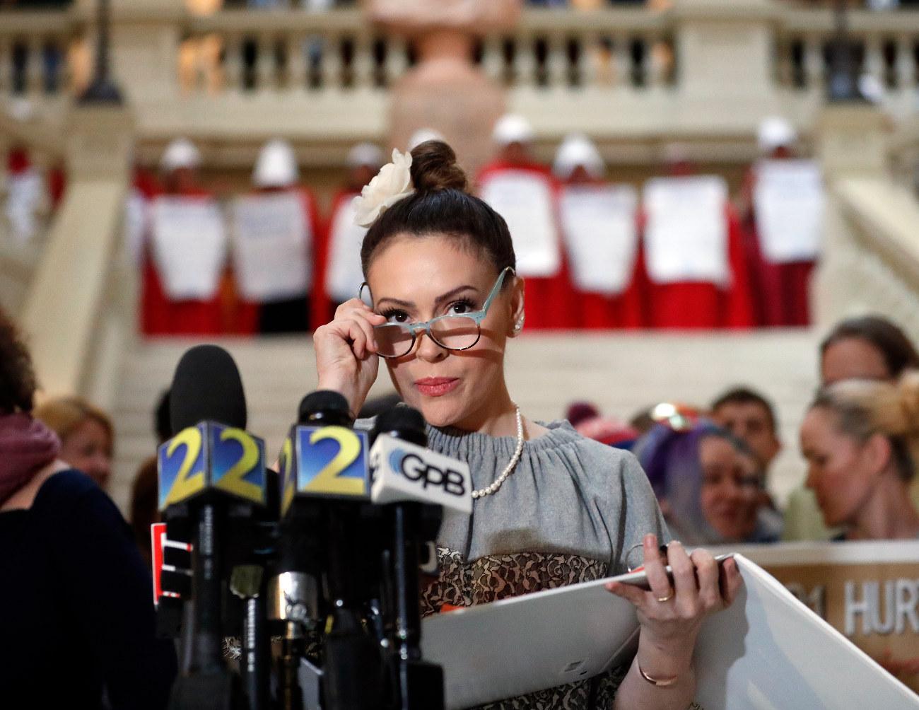 Η Αλίσα Μιλάνο κρατά τα γυαλιά οράσεως στα χέρια της ενώ απευθύνεται σε ΜΜΕ