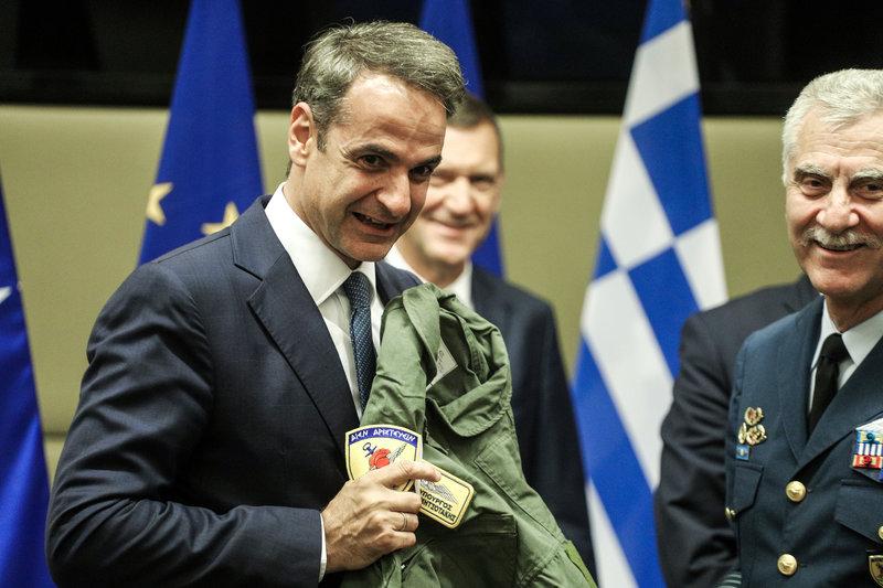 Ο Κ. Μητσοτάκης δείχνει το όνομά του στην στολή πιλότου μαχητικού που του χάρισε ο ΑΓΕΕΘΑ