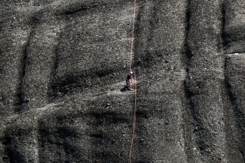 Οι -σχεδόν κάθετοι- σκουρόχρωμοι βράχοι που στέκονται ολόρθοι στην κοιλάδα της Καλαμπάκας -