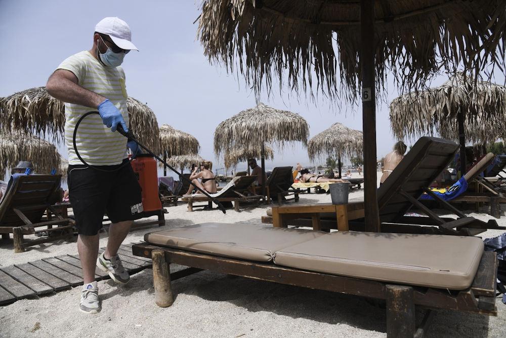Άνδρας ψεκάζει ξαπλώστρες σε παραλία, για την προστασία μετάδοσης από τον κορωνοϊό / Φωτογραφία: Konstantinos Tsakalidis / SOOC