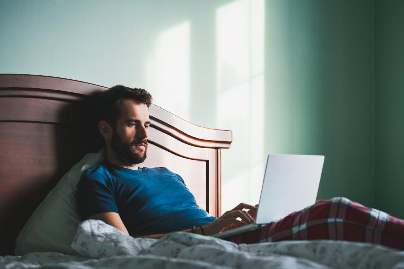 άνδρας με λάπτοπ στο κρεβάτι