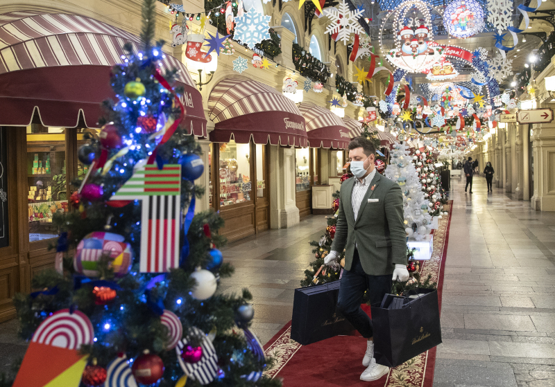 άνδρας με μάσκα και γάντια κρατά τσάντες σε στολισμένο για τα Χριστούγεννα κατάστημα