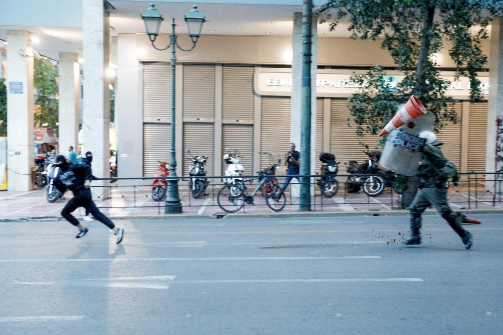Διαδηλωτής τρέχει μπροστά από άνδρα των ΜΑΤ στη Σταδίου