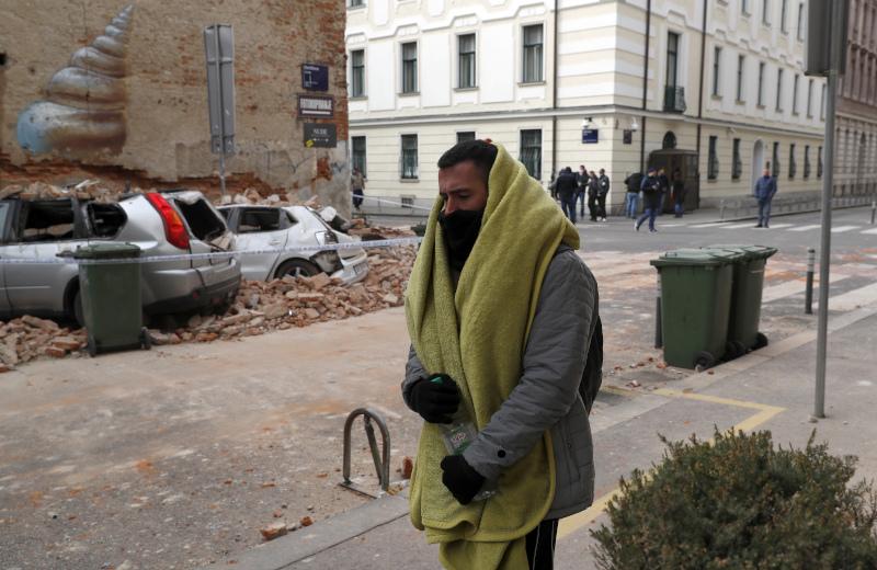 Ένας άνδρας περπατά μπροστά από ένα γκρεμισμένο κτίριο