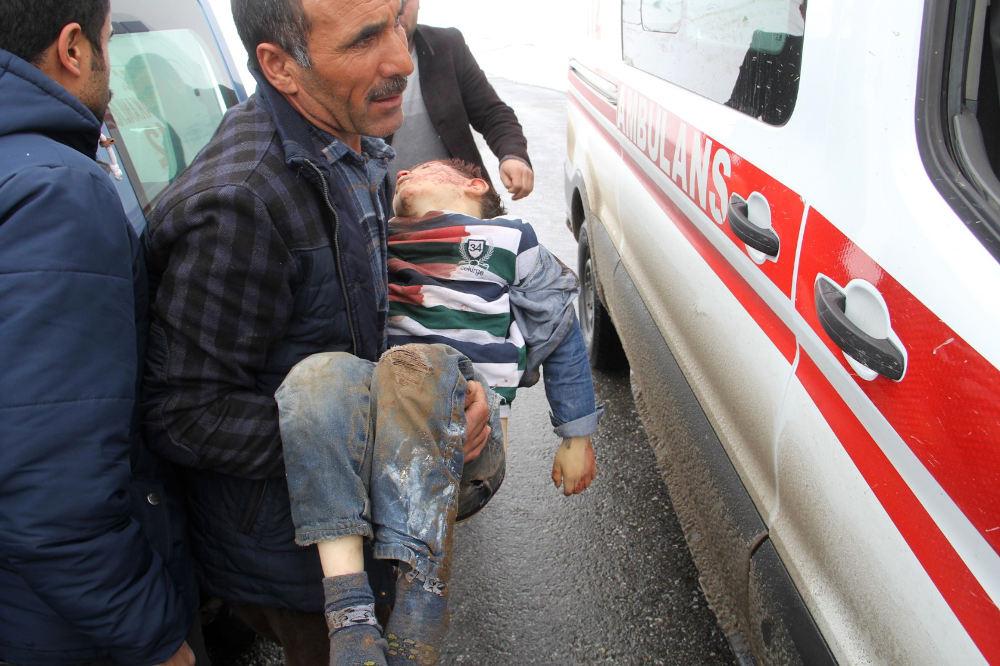 Άνδρας κρατάει στην αγκαλιά του ένα παιδί που τραυματίστηκε από τον σεισμό στην επαρχία Βαν, της Τουρκίας