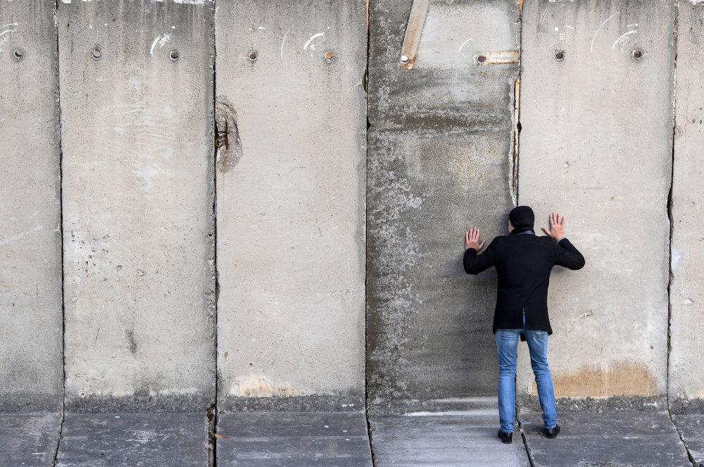 Άνδρας κοιτά από τις χαραμάδες του τείχους σε δρώμενο για την επέτειο των 30 χρόνων από την πτώση του Τείχους του Βερολίνου