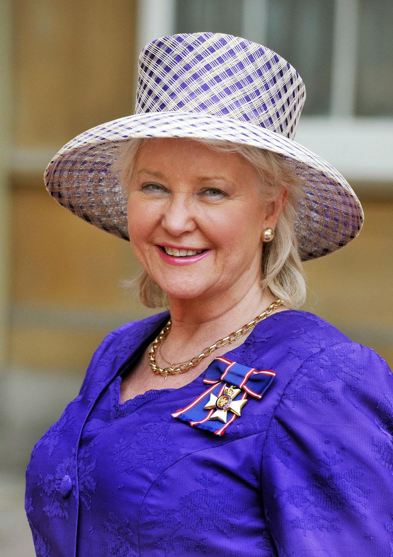 Το δεξί χέρι της βασίλισσας Ελισάβετ, Άντζελα Κέλι  με μοβ σακάκι και καπέλο