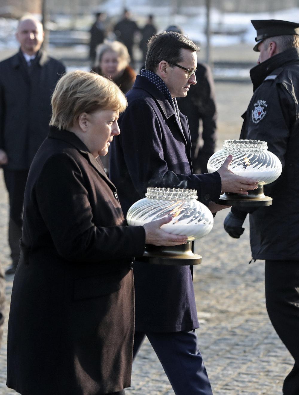 Μέρκελ και Μοραβιέτσκι με κεριά στα χέρια μπροστά από το μνημείο των νεκρών του Άουσβιτς εντός του στρατοπέδου