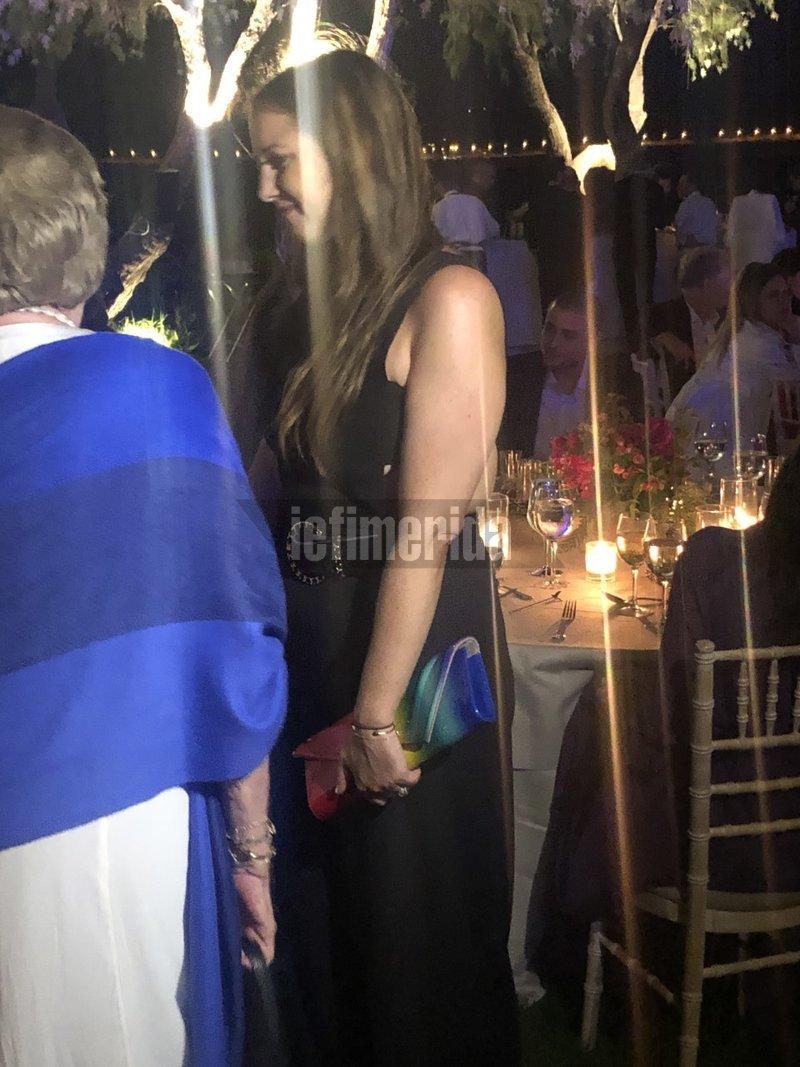 Η Θεοδώρα Γλίξμπουργκ με μαύρο φόρεμα με κοψίματα στα πλαϊνά και clutch με τα χρώματα της ίριδας